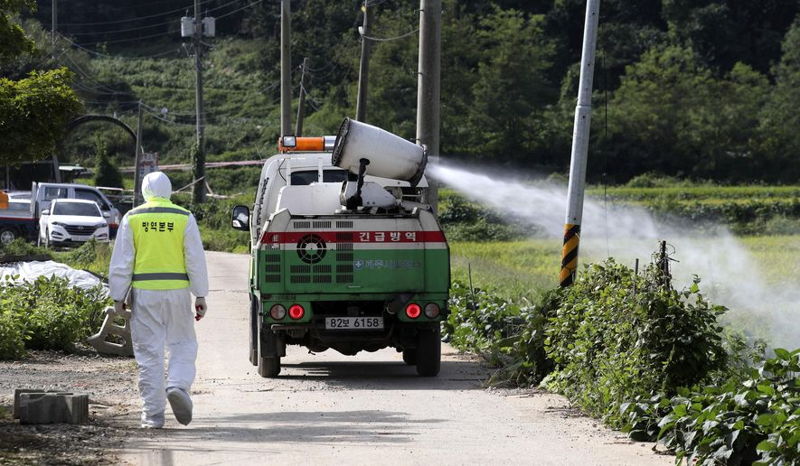 Disinfectant solution is sprayed from a vehicle as a precaution against African swine fever at a pig farm in Paju, South Korea, Tuesday, Sept. 17, 2019. South Korea is culling thousands of pigs after confirming African swine fever at a farm near its border with North Korea, which had an outbreak in May. (Lim Byung-shick/Yonhap via AP)