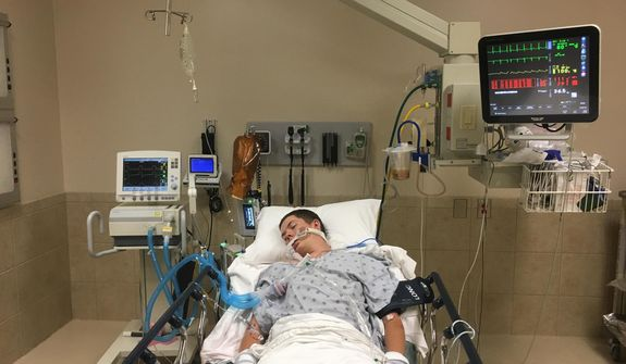 This May 2018 photo provided by Joseph Jenkins shows his son, Jay, in the emergency room of the Lexington Medical Center in Lexington, S.C. Jay Jenkins suffered acute respiratory failure and drifted into a coma, according to his medical records, after he says he vaped a product labeled as a smokable form of the cannabis extract CBD. Lab testing commissioned as part of an Associated Press investigation into CBD vapes showed the cartridge that Jenkins says he puffed contained a synthetic marijuana compound blamed for at least 11 deaths in Europe.  (Joseph Jenkins via AP)