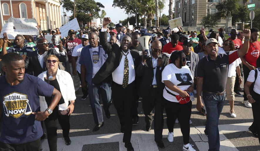 """Attorney Benjamin Crump, center, chants """"Justice for Donald Neely,"""" as he and Bishop James Dixon, pastor of The Community Of Faith Church in Houston, lead a march down 23rd Street in Galveston, Texas, Sunday, Sept. 15, 2019. About 250 demonstrators joined Crump and Dixon to demand the release of police body camera videos related to the Aug. 3 arrest of Neely, who was handcuffed, attached to a lead, and then walked to a staging area between the officers' two horses. (Jennifer Reynolds/The Galveston County Daily News via AP)"""