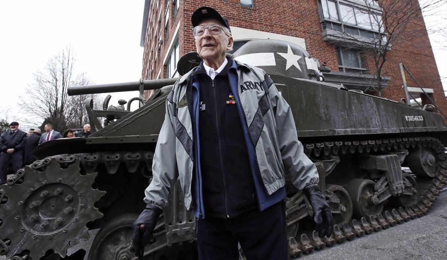 World War II tank gunner Clarence Smoyer poses for a portrait near the Charlestown Naval Shipyard in Boston, Wednesday, Feb. 20, 2019. The 95-year-old veteran was surprised with a ride through the streets of Boston in a Sherman tank, one of the tanks most widely used by the U.S. during the war. (AP Photo/Charles Krupa)