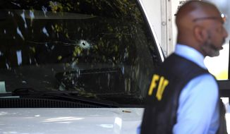 FILE - In this Thursday, Sept. 5, 2019, file photo, a bullet hole can be seen in the front window of a box truck where law enforcement officers investigate after shots were fired involving Immigration and Customs Enforcement agents in the parking lot of a Food Lion store, in the Antioch neighborhood of Nashville, Tenn. Jose Fernando Andrade-Sanchez, a Mexican man who was shot by immigration agents in Tennessee while fleeing a traffic stop on Sept. 5, has been detained and charged with illegal reentry. (Shelley Mays/The Tennessean via AP, File)