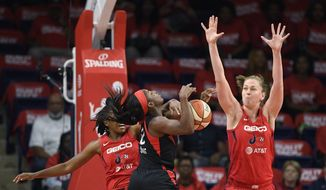 Washington Mystics guard Ariel Atkins, back left, fouls Las Vegas Aces guard Jackie Young (0) during the first half of Game 1 of a WNBA playoff basketball series Tuesday, Sept. 17, 2019, in Washington. Mystics center Emma Meesseman is at right. (AP Photo/Nick Wass)