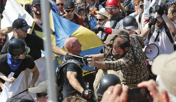 In this Aug. 12, 2017 file photo, white nationalist demonstrators clash with counter-demonstrators at the entrance to Lee Park in Charlottesville, Va.  (AP Photo/Steve Helber, File) **FILE**