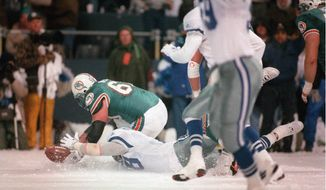 FILE - In this Nov. 25, 1993, file photo, Dallas Cowboys' Leon Lett (78) and Miami Dolphins' Bert Weidner (60) reach for a ball after Lett slides into the ball after the Cowboys blocked a field goal attempt in the snow during an NFL football game in Irving, Texas. After Lett touched the ball the Dolphins recovered and then kicked again for the 16-14 win. (Star-Telegram via AP)