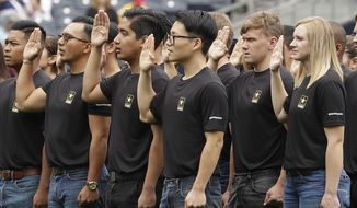 FILE - In this June 4, 2017, file photo. nNew Army recruits take part in a swearing in ceremony before a baseball game between the San Diego Padres and the Colorado Rockies in San Diego. A year after failing to meet its enlistment goal for the first time in 13 years, the U.S. Army is now on track to meet a lower 2019 target after revamping its recruitment effort. (AP Photo/Gregory Bull, File)