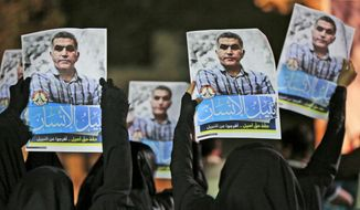 FILE - In this May 14, 2015 file photo, Bahraini anti-government protesters hold up images of jailed human rights activist Nabeel Rajab during a solidarity protest outside his home in Bani Jamra, Bahrain. The Bahrain Institute for Rights and Democracy said Tuesday, Sept. 17, 2019, that a court in Bahrain has refused to release and allow a Rajab to serve the remainder of his five-year prison sentences for tweets at home. (AP Photo/Hasan Jamali, File)