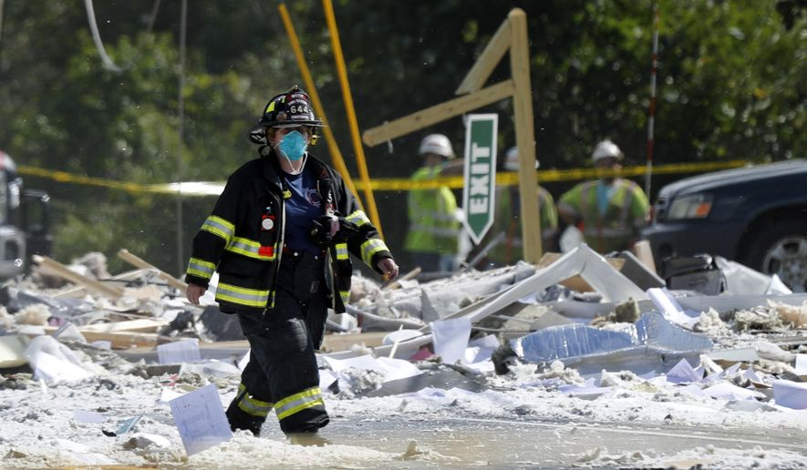 A firefighter walks through the scene of an explosion Monday, Sept. 16, 209, in Farmington, Maine. Officials say a town's fire chief is among the injured in a propane explosion that killed a firefighter. State public safety spokesman Steve McCausland said after Monday morning's explosion at a nonprofit center in Farmington that multiple people remain hospitalized. (AP Photo/Robert F. Bukaty)