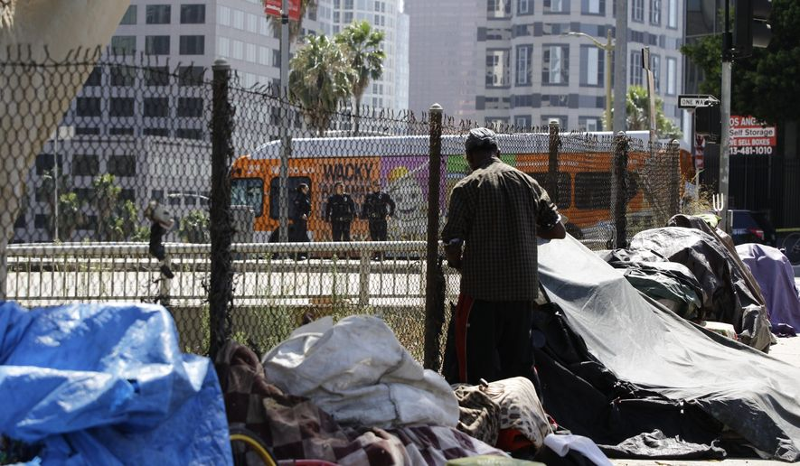 """A newly displaced homeless camp is seen while Los Angeles Police officers guard a Harbor Freeway ramp during the visit of President Donald Trump in Los Angeles, Tuesday, Sept. 17, 2019. Trump began a California visit on Tuesday, saying he will do """"something"""" about homelessness but offering no specifics beyond the mention of creating a task force. (AP Photo/Damian Dovarganes)"""