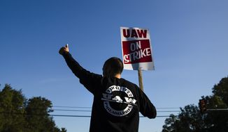 A worker gives the thumbs-up gesture to a passing motorist as he demonstratives outside a General Motors facility in Langhorne, Pa., Tuesday, Sept. 17, 2019. More than 49,000 members of the United Auto Workers walked off General Motors factory floors or set up picket lines early Monday as contract talks with the company deteriorated into a strike. (AP Photo/Matt Rourke)