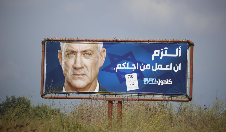 "An election campaign billboard shows the Blue and White party leader Benny Gantz, in the Arab town of Baqa al-Gharbiyye, northern Israel, Monday, Sept. 16, 2019. The Arab writing says, "" I commit to work for you.""  Israel will hold general elections on Tuesday. (AP Photo/Ariel Schalit)"