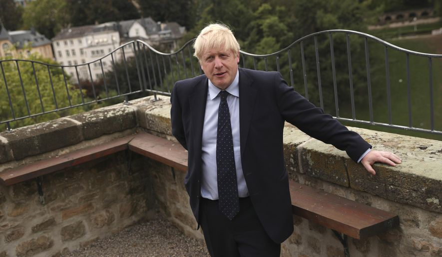 British Prime Minister Boris Johnson poses for photographers on the balcony of the UK ambassadors residence prior to giving a statement to television after a meeting with Luxembourg's Prime Minister Xavier Bettel in Luxembourg, Monday, Sept. 16, 2019. (AP Photo/Francisco Seco, Pool)