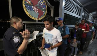 Cuban Abel Oset Jr., center, and his father Abel Oset, behind him, show their identification to a U.S. Customs and Border Protection officer before their appointments to apply for asylum in United States, as they cross International Bridge 1 to leave Nuevo Laredo, Mexico and enter Laredo, Texas, Tuesday, Sept. 17, 2019. Tent courtrooms opened Monday in two Texas border cities to help process thousands of migrants who are being forced by the Trump administration to wait in Mexico while their requests for asylum wind through clogged immigration courts. (AP Photo/Fernando Llano)