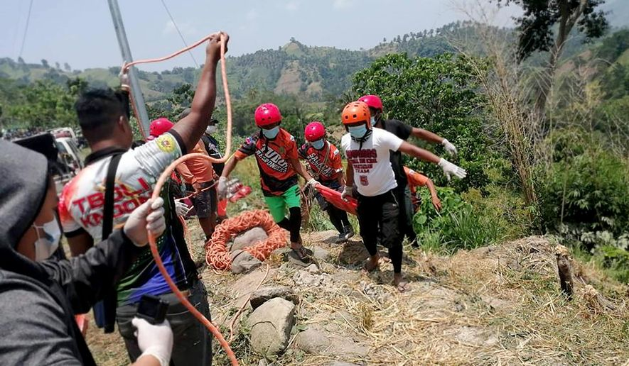 In this photo provided by the Philippine Red Cross, Red Cross volunteers retrieve the bodies of victims following a road accident Tuesday, Sept. 17, 2019, in a remote village in the Tboli township, South Cotabato in the southern Philippine.  At least 15 people were killed and several others injured when a truck's brakes apparently failed and plummeted down a ravine. (Philippine Red Cross, South Cotabato Chapter Via AP)