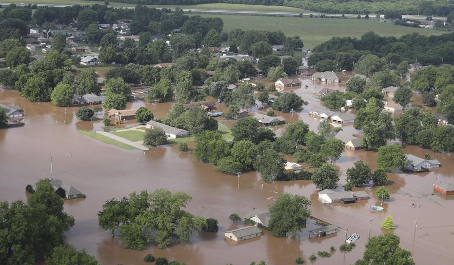 FILE -- In this May 24, 2019 file photo, homes are flooded near South 145th West Ave. near Oklahoma 51 on the Arkansas River in Tulsa, Okla. The U.S. Army Corps of Engineers has proposed a $160 million plan to shore up the 75-year-old Tulsa-West Tulsa Levee System, a system of levees and pumping stations around Oklahoma's second largest city that has been weakened by periodic flooding. (Tom Gilbert/Tulsa World via AP, File)