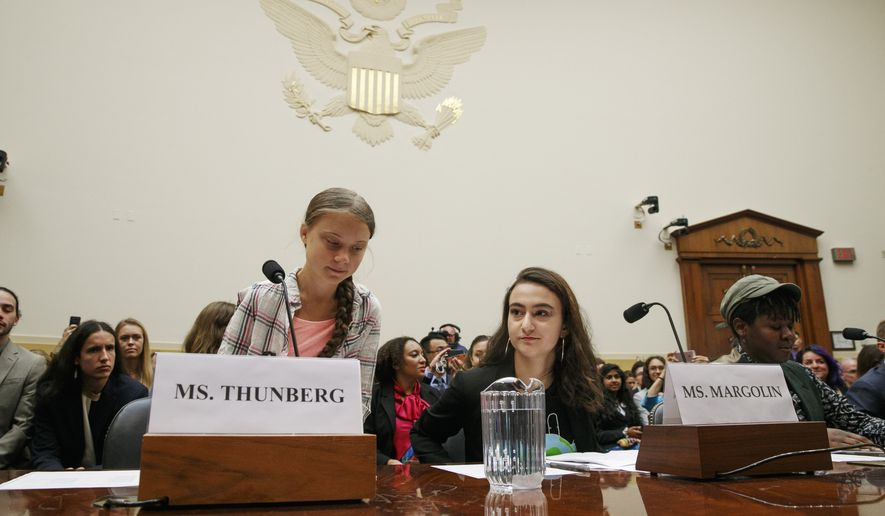 Youth climate change activist Greta Thunberg, left, takes her seat to testify at a House Foreign Affairs Committee subcommittee hearing on climate change Wednesday, Sept. 18, 2019, on Capitol Hill in Washington. (AP Photo/Jacquelyn Martin)