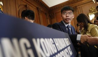 Hong Kong activist Joshua Wong, hands out his business card following a news conference on human rights in Hong Kong on Capitol Hill in Washington, Wednesday, Sept. 18, 2019. (AP Photo/Pablo Martinez Monsivais)