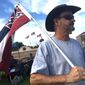 Joe Waites, a member of the No State Flag/No State Funds protest group, holds the Mississippi State flag outside the front gate of the University of Southern Mississippi, where the group has gathered every Sunday for nearly four years to protest USM's refusal to unfurl the state flag. (Chuck Cook/Special to The Washington Times)