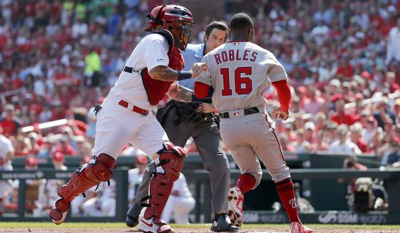 Washington Nationals' Victor Robles (16) is tagged out at home by St. Louis Cardinals catcher Yadier Molina during the second inning of a baseball game Wednesday, Sept. 18, 2019, in St. Louis. (AP Photo/Jeff Roberson)
