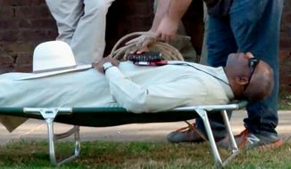 FILE - In this April 17, 2018, file image from video provided by KTHV-TV, a death penalty protester outside the Arkansas governor's mansion in Little Rock prepares to tie rope around Pulaski County Circuit Judge Wendell Griffen who is laying on a cot in protest of executions. Arkansas' attorney general is asking the state Supreme Court to reassign cases involving her office from a judge who's been prohibited from handling execution cases, accusing him of regularly being biased against her staff. Attorney General Leslie Rutledge on Tuesday, Sept. 17, 2019, requested that the court reassign the civil cases from Pulaski County Circuit Judge Wendell Griffen, who was prohibited from handling execution cases in 2017 after he participated in an anti-death penalty demonstration.(KTHV/TEGNA Inc. via AP, File)