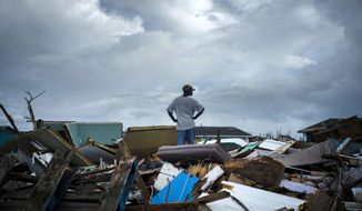 A man stands on the rubble of his home in the Haitian Quarter, after the passage of the Hurricane Dorian in Abaco, Bahamas, Monday, Sept. 16, 2019. Dorian hit the northern Bahamas on Sept. 1, with sustained winds of 185 mph (295 kph), unleashing flooding that reached up to 25 feet (8 meters) in some areas. (AP Photo/Ramon Espinosa)