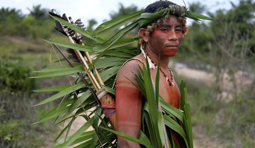 Indigenous Tembe warrior Ronilson Tembe poses for a portrait on the Alto Rio Guama indigenous reserve as he waits for police to arrive with other members of his tribe in Para state, Brazil, Wednesday, Sept. 4, 2019.  Tembe men sometimes daub themselves in traditional war paint and patrol the forest. They carry bows and arrows, but feel increasingly vulnerable as they brace for run-ins with illegal loggers. (AP Photo/Luis Andres Henao)