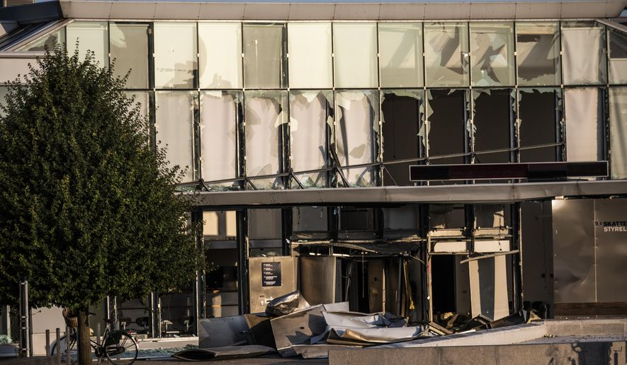 FILE - This Wednesday, Aug. 7, 2019 file photo, shows a view of the damage caused by an explosion to the entrance of the Danish Tax Authority in Copenhagen, Denmark. Police in Denmark say they have arrested a 23-year-old man late Tuesday Sept. 17, 2019, as a suspect in the explosion that damaged the headquarters of the Danish Tax Agency and slightly injured a bystander last month. (Olafur Steinar Rye Gestsson/Ritzau Scanpix via AP, File)
