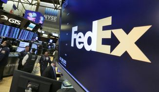 FILE- In this Feb. 9, 2018, file photo the logo for FedEx appears above a trading post on the floor of the New York Stock Exchange.  FedEx shares tumbled after the delivery giant blamed slowing economic growth and trade tension for a disappointing quarter and cut its forecast of full-year earnings. Shares were down $23.67, or 13.7%, to $149.63 in afternoon trading Wednesday, Sept. 18, 2019.  (AP Photo/Richard Drew, File)