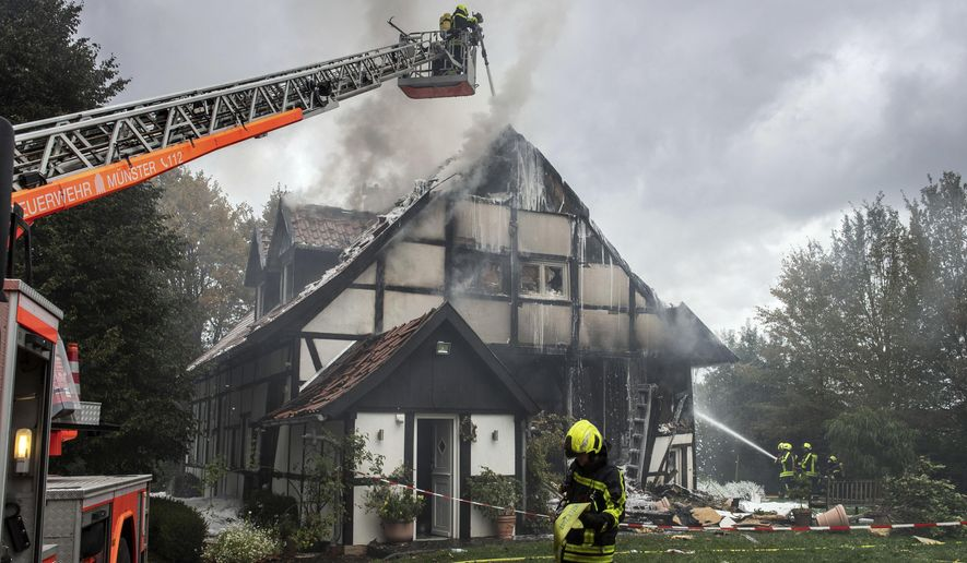 Firefigthers extinguish a fire in a house in Muenster, Germany, Wednesday, Sept. 18, 2019. Two women and a police officer where injured by an exploion inside the house. (Bernd Thissen/dpa via AP)