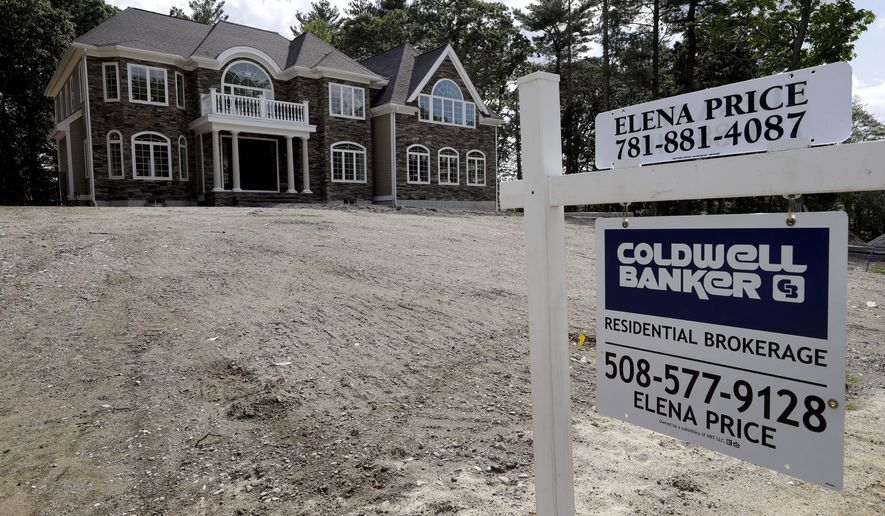In this Tuesday, Sept. 3, 2019 photo a sign rests in front of a newly constructed home, in Westwood, Mass. On Wednesday, Sept. 18, the Commerce Department reports on U.S. home construction in August. (AP Photo/Steven Senne)