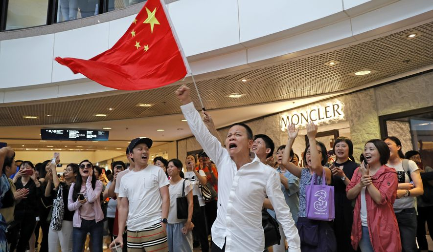 Pro-China supporters wave a Chinese national flag in a shopping mall in Hong Kong, Wednesday, Sept. 18, 2019. Activists involved in the pro-democracy protests in Hong Kong appealed to U.S. lawmakers Tuesday to support their fight by banning the export of American police equipment that is used against demonstrators and by more closely monitoring Chinese efforts to undermine civil liberties in the city. (AP Photo/Kin Cheung)