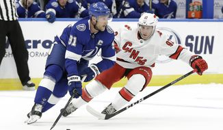 Tampa Bay Lightning center Steven Stamkos (91) looks to pass the puck around Carolina Hurricanes forward Colin Markison (92) during the first period of an NHL preseason hockey game Tuesday, Sept. 17, 2019, in Tampa, Fla. (AP Photo/Chris O'Meara)