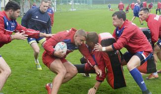 In this Aug. 9, 2019, photo, Russian rugby players work out in a camp on the outskirts of Moscow, ahead of the Rugby World Cup starting in Japan in September. Japan will have its first taste of the expectation which comes with being tournament host when it plays Russia in the opening match of the first Rugby World Cup to be held in Asia. An upset win over South Africa at the last World Cup swelled Japan's fan-base at home and abroad and has added to the expectation that they may be the giant-killers of this year's tournament. (Kyodo News via AP)
