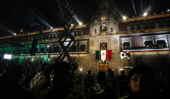 """Police provide a security cordon as President Andres Manuel Lopez Obrador and first lady Beatriz Gutierrez Muller look out toward the crowd from the balcony of the National Palace, after Lopez Obrador gave the annual independence shout to kick of Independence Day celebrations at the Zocalo in Mexico City, Sunday, Sept. 15, 2019. Every year the Mexican president marks the """"Grito de Dolores,"""" commemorating the 1810 call to arms by priest Miguel Hidalgo that began the struggle for independence from Spain, achieved in 1821.(AP Photo/Rebecca Blackwell)"""