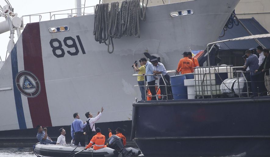 FILE - In this May 28, 2013, file photo, Taiwanese investigators ride a rubber boat as they inspect a ship involved in the alleged shooting of a Taiwanese fisherman while they continue their probe in Manila, Philippines. A Philippine court found eight Filipino coast guard personnel guilty Wednesday, Sept. 18, 2019 of conspiring to shoot and kill a Taiwanese fisherman in a 2013 incident at sea that strained ties between the neighboring nations. (AP Photo/Aaron Favila, File)