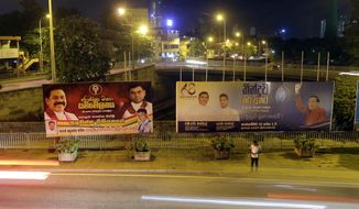A Sri Lankan man stands near billboards displaying President Maithripala Sirisena, right, and former president Mahinda Rajapaksa, left, in Colombo, Sri Lanka, Wednesday, Sept. 18, 2019. Sri Lanka will hold a presidential election on Nov. 16, the elections office said Wednesday, amid calls for a strong leader to boost national security as the country recovers from deadly Easter Sunday bomb attacks. (AP Photo/Eranga Jayawardena)