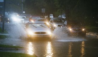 Vehicles splash through heavy water filling Chimney Rock, south of Brays Bayou in Houston, Tuesday, Sept. 17, 2019. Officials in the Houston area were preparing high-water vehicles and staging rescue boats Tuesday as Tropical Storm Imelda moved in from the Gulf of Mexico, threatening to dump up to 18 inches of rain in parts of Southeast Texas and southwestern Louisiana over the next few days. (Mark Mulligan/Houston Chronicle via AP)
