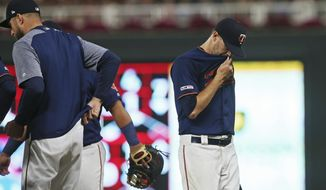 Minnesota Twins pitcher Jake Odorizzi, right is pulled by manager Rocco Baldelli, left, in the sixth inning of a baseball game against the Chicago White Sox Wednesday, Sept. 18, 2019, in Minneapolis. (AP Photo/Jim Mone)