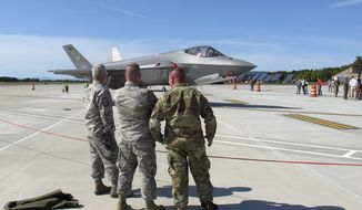 Three National Guard members look at the first two F-35 fighter jets that arrived on Thursday, Sept. 19, 2019, at the Vermont Air National Guard base in South Burlington, Vt., flown by guard pilots to Vermont from the factory in Fort Worth, Texas. The Vermont Air National Guard is the first guard unit in the country to receive the next-generation fighter. (AP Photo/Wilson Ring)