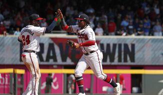 Atlanta Braves center fielder Ronald Acuna Jr., right, and second baseman Adeiny Hechavarria (24) celebrate after defeating Philadelphia Phillies. 5-4 in a baseball game Thursday, Sept. 19, 2019, in Atlanta. (AP Photo/John Bazemore)