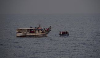 A fishing boat throws water bottles to migrants on an overcrowded wooden boat in the Mediterranean Sea, Thursday, Sept. 19, 2019. The Ocean Viking, jointly operated by SOS Mediterranee and Doctors Without Borders, rescued 36 people from the small wooden boat after being requested to do so by Maltese authorities. (AP Photo/Renata Brito)