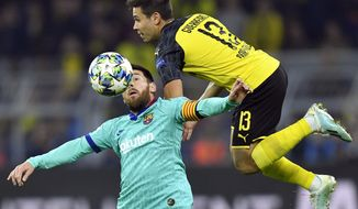 Barcelona's Lionel Messi, left, fights for the ball with Dortmund's Raphael Guerreiro during the Champions League Group F soccer match between Borussia Dortmund and FC Barcelona in Dortmund, Germany, Tuesday Sept. 17, 2019. (AP Photo/Martin Meissner)
