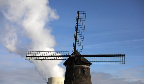 Steam rises from a nuclear power station behind an old windmill on the River Scheldt in Doel, Belgium, Thursday, Sept. 19, 2019. Political leaders meet Sept. 23, 2019, for a climate summit in New York to ramp up global efforts to tackle the climate crisis. (AP Photo/Virginia Mayo)