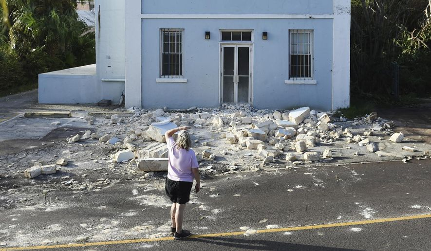 A woman looks up at a building damaged by Hurricane Humberto in Blue Hole Park, Bermuda, Thursday, Sept. 19, 2019. Humberto blew off rooftops, toppled trees and knocked out power but officials said Thursday that the Category 3 storm caused no reported deaths. (AP Photo/Akil J. Simmons) ** FILE **