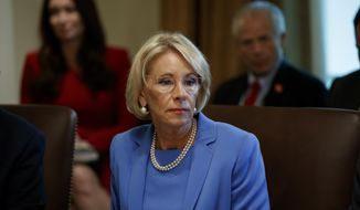 """In this July 16, 2019, file photo, Education Secretary Betsy DeVos listens during a Cabinet meeting in the Cabinet Room of the White House in Washington. The Trump administration is threatening to cut grant funding to a Middle East studies program at the University of North Carolina and Duke University, saying it's misusing federal funding to advance """"ideological priorities"""" and unfairly promotes """"the positive aspects of Islam"""" but not Christianity or Judaism. (AP Photo/Alex Brandon, File)"""