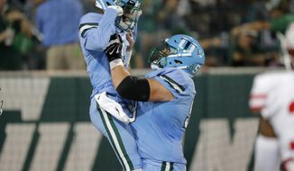 Houston wide receiver Bryson Smith, left, celebrates his touchdown with offensive lineman Christian Montano during the first half of an NCAA college football game against Tulane in New Orleans, Thursday, Sept. 19, 2019. (AP Photo/Gerald Herbert)