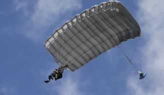 Tom Rice, a 98-year-old American WWII veteran, front left, approaches the landing zone during a tandem parachute jump near Groesbeek, Netherlands, Thursday, Sept. 19, 2019, as part of commemorations marking the 75th anniversary of Operation Market Garden. Rice jumped with the U.S. Army's 101st Airborne Division in Normandy, landing safely despite catching himself on the exit and a bullet striking his parachute. (AP Photo/Peter Dejong)