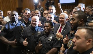 Vice President Mike Pence, second from right, meets with members of the New York Police Department's football team, Thursday, Sept. 19, 2019. Pence met earlier with the NYPD for a counterterrorism briefing. (AP Photo/Mark Lennihan)