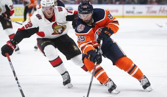 FILE - In this March 23, 2019, file photo, Ottawa Senators' Thomas Chabot, left, checks Edmonton Oilers' Sam Gagner, right, during second-period NHL hockey game action in Edmonton, Alberta. Chabot has agreed to an eight-year, $64 million contract extension. (Jeff McIntosh/The Canadian Press via AP, File)