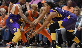 Connecticut Sun's Courtney Williams, center, passes between Los Angeles Sparks' Riquna Williams, left, and Candace Parker during the first half of Game 2 of a WNBA basketball playoff game Thursday, Sept. 19, 2019, in Uncasville, Conn. (AP Photo/Jessica Hill)