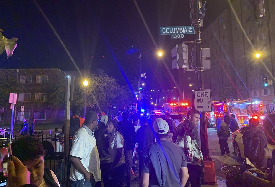 In this photo provided by Peter Sacco, a crowd gathers at a cordoned-off intersection near a shooting Thursday, Sept. 19, 2019, in a Washington, D.C., neighborhood. Police say one man was killed and five other adults were wounded in a shooting in the courtyard of an apartment complex near Columbia Heights Metro Station in the nation's capital. (Peter Sacco via AP)